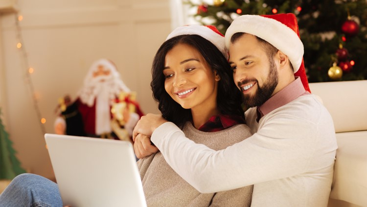 couple in Santa hats sitting on the sofa christmas laptop movie