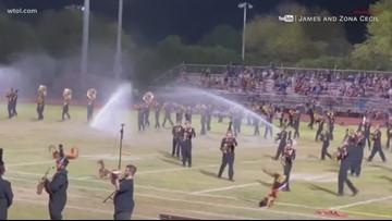 Surprise! Sprinklers soak band members on the field in Arizona